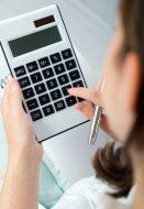 kobieta-trzyma-pioro-i-naciskając-przyciski-kalkulatora_1301-2658